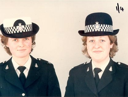 Woman Police Constables Felicity Dunkerley and Frances Bingham modelling the 2 different types of hats for policewomen  - at change over from old style white hat to hardened bowler Autumn 1985. (Gloucestershire Police Archives URN 440)