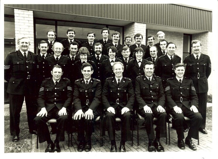 C Shift Bamfurlong, and senior officers. 1979. Back row left to right: Chris Meadows; Tony Russ; Mike O'Neill; Dave Pedrick; Clive Kibble; Steve Ashton; Andy Isko; Richard Bradley; Steve Norgate; Dave Causon. Centre row left to right: Police Sergeant Roy Thomas; Bryn Wilkinson; Ray Jones; Martin Cordwell; Sharon Jones; Pete James; Jean Wilson;Chris Holland;Sue Johns: Pete Edwards; Ray Fortey; Police Sergeant Dave Thompson. Front row left to right: Police Sergeant Don Say; Inspector Harold Clark; Superintendent  Alan Bobs; Inspector  Brian Brazil; Police Sergeant Jim Tidmarsh. (Gloucestershire Police Archives URN 163)