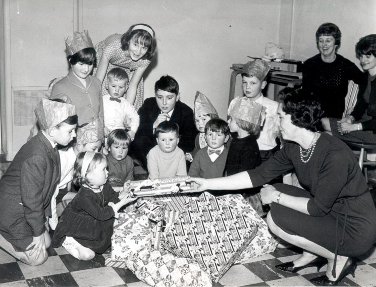 Police children's Christmas Party at Dursley Police Station with prizes being handed out by Barbara Parker (wife of Chief Inspector Bob Parker).  Also in picture Mrs Val Hillier, Anne Parker, Martin Parker, Martyn Hillier, 1965. (Gloucestershire Police Archives URN 1008)