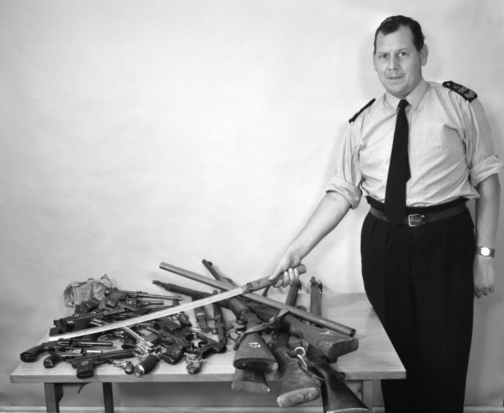 Sergeant Mike Perry with firearms handed in at a firearms amnesty session. (Gloucestershire Police Archives URN 1077)
