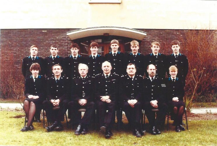 Last intake of Regular Police Cadets. Left to right back row:  Jon Weager, Dave Thompson,  Tim Cook,  Ian Viles,  Jared Hughes,  Craig Guthrie,  Keith Smith,  Andy Christopher. Front row Rachel Price,  Police Constable David Stacey,  Inspector  Alan Billinghurst,  Chief Inspector Alan Beckett,   Inspector Jeffery Spinks,  Police Sergeant Roy Palmer,  Joanne Waite, September 1983. (Gloucestershire Police Archives URN 1149)