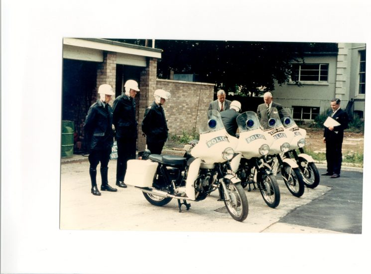 Inspection of the two  new Triumph 650cc 'Saints' motor-cycles at rear of Headquarters. The two Motorcycles on the far right are BSA A65 650cc twins which the force were trying out but they were not a success so more Triumphs were purchased. Left to right: Police Constables Tony Hughes,  Adrian Wallace, unknown, Brian Bailey .Superintendent Paul Foice, Assistant Chief Constable 'Herbie' Smith and Chief Inspector Arthur Meadows. (Gloucestershire Police Archives URN 1169)