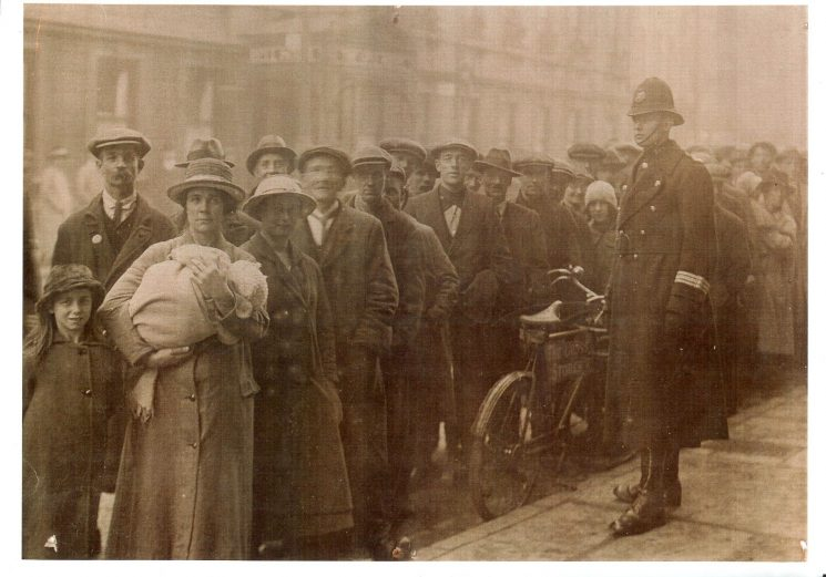Police Constable Morton Fluck on duty controlling a queue in  Southgate Street Gloucester with the Bell Hotel in the background. The queue are recipients of the Mayors fund, thought to be in December 1921. The unemployed waiting for a hand out of food for Christmas in the old Corn Exchange building behind the Southgate Street Post Office. (Gloucestershire Police Archives URN 1197) | Thanks to Tony Conder for the additional information