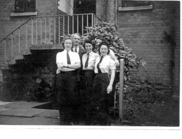 One Police Constable, one Woman Police Constable  and three Woman Auxiliary Police Constables at rear of Cheltenham Police Station Crescent Terrace. Left to right: Woman Auxiliary Police Constable Dorothy HALE  (now GARDNER), Police Constable  John ANGUS, Woman Auxiliary Police Constable Joyce PAYTON (now MOORE), Woman Police Constable Laura BALL (now CLARKE), Woman Auxiliary Police Constable Doreen WEBB (now SINCLAIR). (Gloucestershire Police Archives URN 1198)