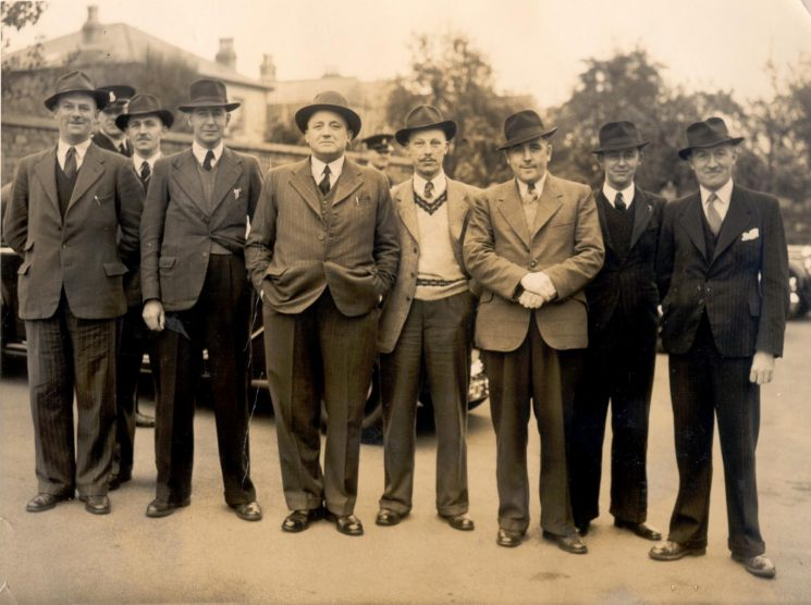 Criminal Investigation Department officers at Staple Hill. left to right Detective Constable Idris Dimery; Police Sergeant  P. Foice (in uniform); Detective Constable Cyril Woodward; Detective Sergeant Len Browning;  Detective Inspector Sid Hyam; Detective Constable Bert Trull; Detective Constable Andy Weir; Police Constable Bill Scudmore; Police Constable  John Hammond. (Gloucestershire Police Archives URN 1235)