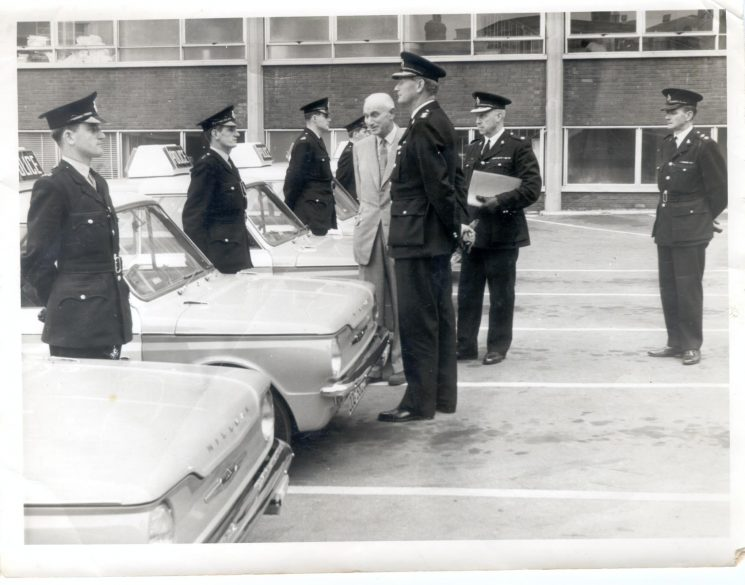 Hillman Imp Panda Cars at Gloucester Police Station. Deputy Chief Constable Herbert Smith, Superintendent V. J. Bullock, Superintendent Bob Mayo, Inspector Sid James, Police Constables Richard Williams, Bruce Trotman, John Worollo, Brian Farmer. (Gloucestershire Police Archives URN 1249)