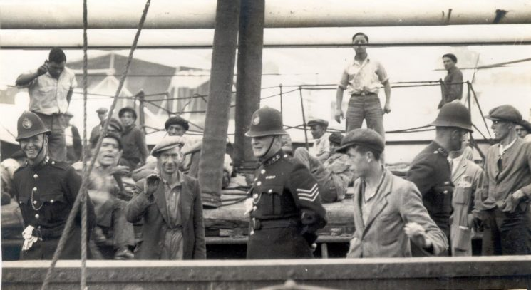 Police on board Spanish Ship Juan de Astigarraga in Sharpness docks as a result of the crew's attitude towards the discharging of the cargo.  The Spanish sailors were averse to the picture being taken. Police Constable  Gay, Police Sergeant Albert Gowell , Police Constable  Gibson. The ship left Sharpness docks on 28.10.1938. (Gloucestershire Police Archives URN 128)