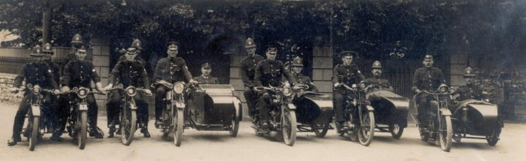 Fifteen uniformed officers on motor cycles and motor cycle combinations during the Forest of Dean Miners strike in 1926. Second from left is Police Constable William H. Chandler.  The officer in the sidecar in the centre of the photo is Inspector Alan Brent of Coleford.  It is believed that most if not all of the motor cycles were the property of the riders. (Gloucestershire Police Archives URN 2385)