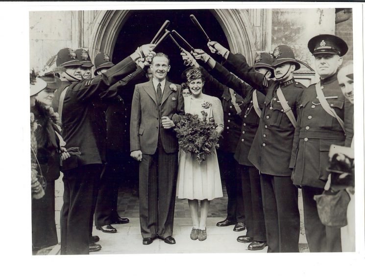 Alex Gait at his wedding to Margaret Pink in September 1941 with group of fellow officers forming a guard of honour with truncheons. (Gloucestershire Police Archives URN 1432)