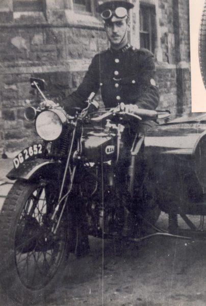 Police Constable Cuthbert A. Smith (Cass) on motor cycle combination DG 2652 at Lydney Police Station 1931. (Gloucestershire Police Archives URN 146)