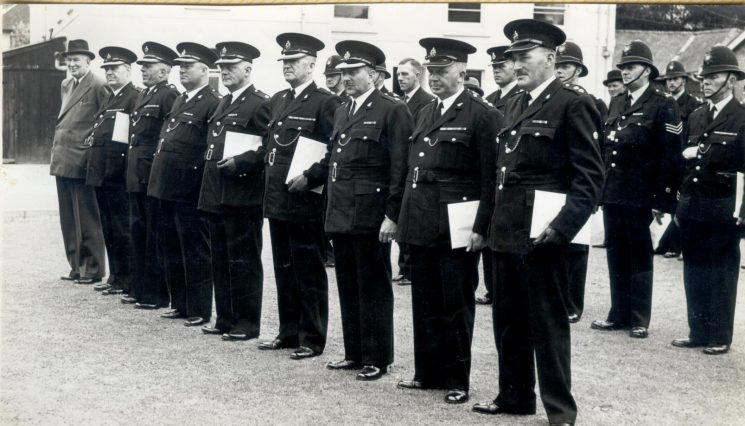Presentation of Coronation medals by Duke of Beaufort 1953 at Holland House. Identified-  Detective Superintendent Hancock;  J. Hallam; W. Hart; C.P. Oakley; S. D. Smith; unknown; A. W. Hopkins; Inspector E. J. Herbert; and N. Baker.  also J. Johnston; P. Foice; D. Deakin. (Gloucestershire Police Archives URN 148)
