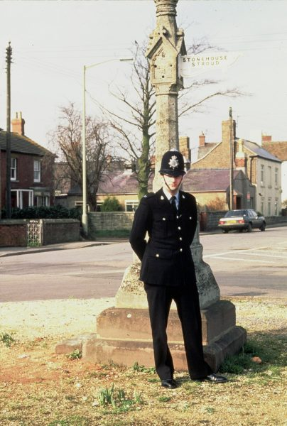 Modern police officer in uniform at the cross in Eastington (Nigel Avron ?). (Gloucestershire Police Archives URN 1555-1)