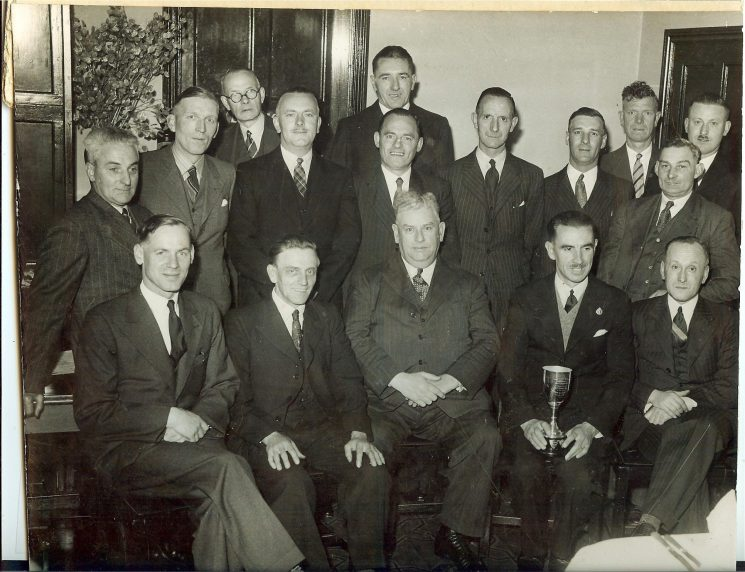 Gloucester Division skittle team taken in Gloucester Police Club. Champions in the Gloucester City 11a League - 1948-1949. Back row left to right:  Special Sergeant A. West; Special Constable S. Toomey; Special Sergeant  J. Pettern; Special Constable R. Bayliss, Special Constable J. Dwyer; Special Constable J.J. Drinkwater; Inspector H. Tredwell; Ex Police War Reserve H. Bundy; Special Constable J. Harris; Special Constable Hyett; Police Constable Rogers. Front row left to right: Police Constable B. Gwilliam; Police Constable T. Edwards; Chief Superintendent W.E. Wakefield; Police Constable H. Thomas; Special Constable A. Kerslake. (Gloucestershire Police Archives URN 1649)