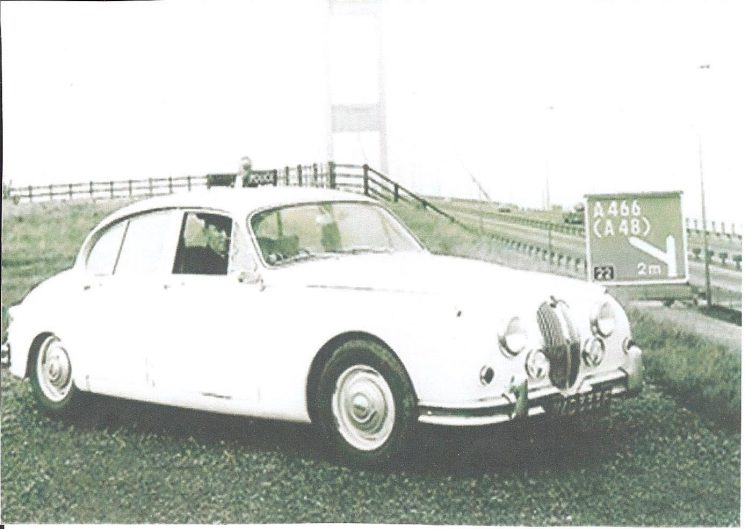 New white Jaguar patrol car  driven by Police Constable Dennis Trayler taken by the Severn bridge. Gloucestershire Constabulary had only one Jaguar  patrol car which operated from the motorway patrol centre in Almondsbury. (Gloucestershire Police Archives URN 1652)