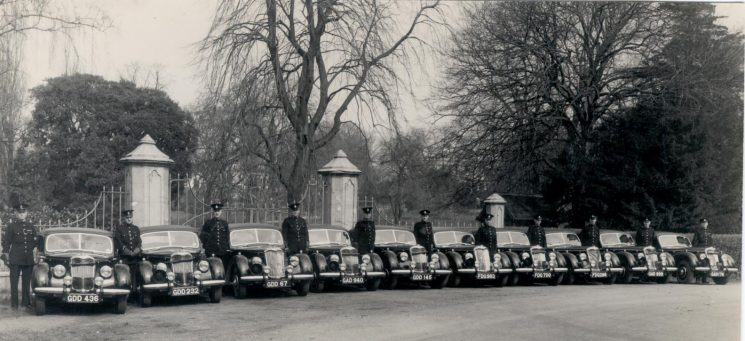 Fleet of Riley Motor Cars at Pittville Park with drivers. Left to right: Cyril Williams, Tom Pugsley, C.A. Smith, Paul Foice, Percy Williams, Chas Nicholls, Clark, Bill Turner, Jack Rogers, Derek Bezant, 1946/7. (Gloucestershire Police Archives URN 178)