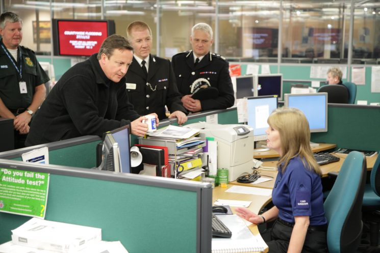 David Cameron, Prime Minister, visiting  Tri-Service Control Room during the  2014 Floods talking to Force Control Room Supervisor Ginny Maslin. Also in photograph  Superintendent Gary Thompson and  Assistant Chief Constable Kevin Lambert. (Gloucestershire Police Archives URN 1855-1)