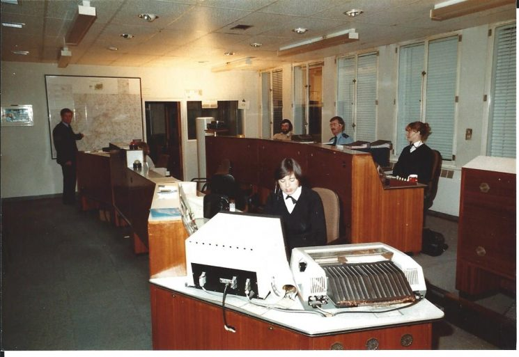 Information Room, Headquarters at Holland House possibly mid- 1980's  (note the sole computer, possibly for Police National Computer). Left to right :  Police Sergeant  Jim Harding, Eric Hood (civilian operator); Woman Police Constable Rose Daly; Police Sergeant  David Thompson (DT); Woman Police Constable Wendy Smith (later Hazlewood). (Gloucestershire Police Archives URN 1959)