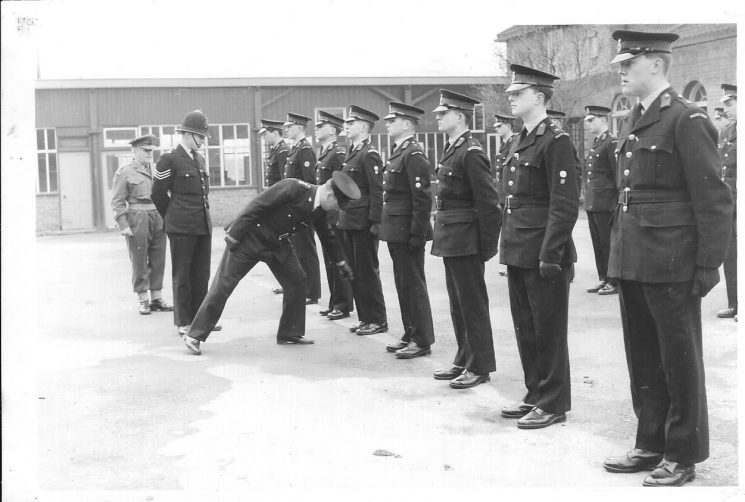 Regular Police Cadets doing drill at Dean Close probably 1961. Left to right: Regimental Sergeant Major Benyon (Dean Close School); Police Sergeant Clark - training branch; Chief Inspector Baker (Inspecting Officer) - training branch; Front row Left to right:  Bryant; David Baker; Pete Kilbey; David Thompson; Brian Bailey; Roger Robinson; Robin Haines, David Agget. Back row left to right: Alan Morey; Ray Trigg; Roger Renault. (Gloucestershire Police Archives URN 1962)