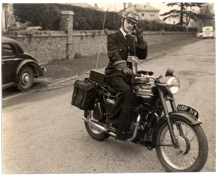 Police Constable D. Webb with Triumph motor cycle UDF 319 at side of Holland House in Talbot Road 1962. (Gloucestershire Police Archives URN 198)