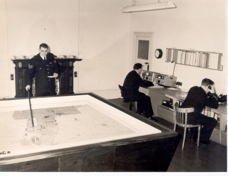 Force Information Room in 1964 Police Sergeant C. J. Davis and two unknown staff. (Gloucestershire Police Archives URN 204)