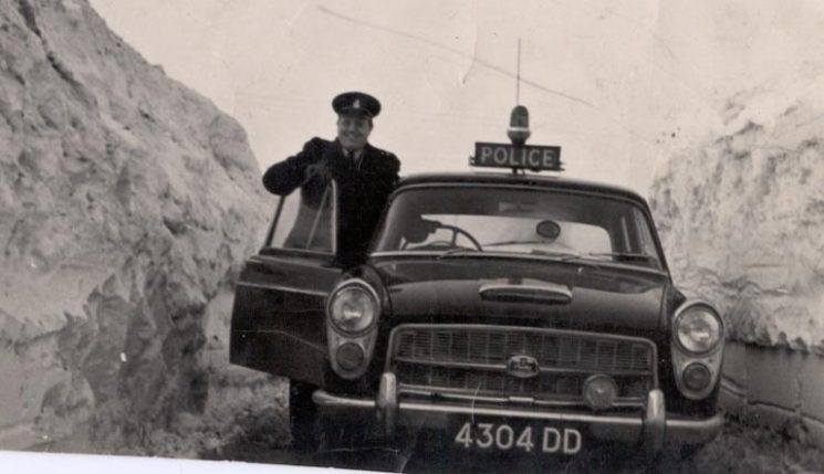 Police Constable A. Laver with Austin patrol car 4304 DD in snow at Hampton Fields, Minchinhampton - Winter 1963. (Gloucestershire Police Archives URN 206)