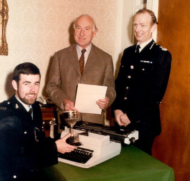 Presentation of Colburn Trophy by Oscar Colburn, Commander British Empire; Justice of the Peace; Deputy Lieutenant to Police Constable Michael Barton  who won the trophy for his essay on Policing with Chief Constable Soper. (Gloucestershire Police Archives URN 370)