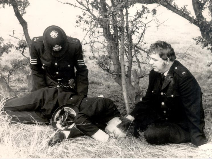 Three officers recovering from injuries at Gascoigne Wood  Mine during Miners Strike 1984. Kim Butcher injured, Neil Thomas kneeling and Sergeant Richard Green administering first aid. (Gloucestershire Police Archives URN 379)