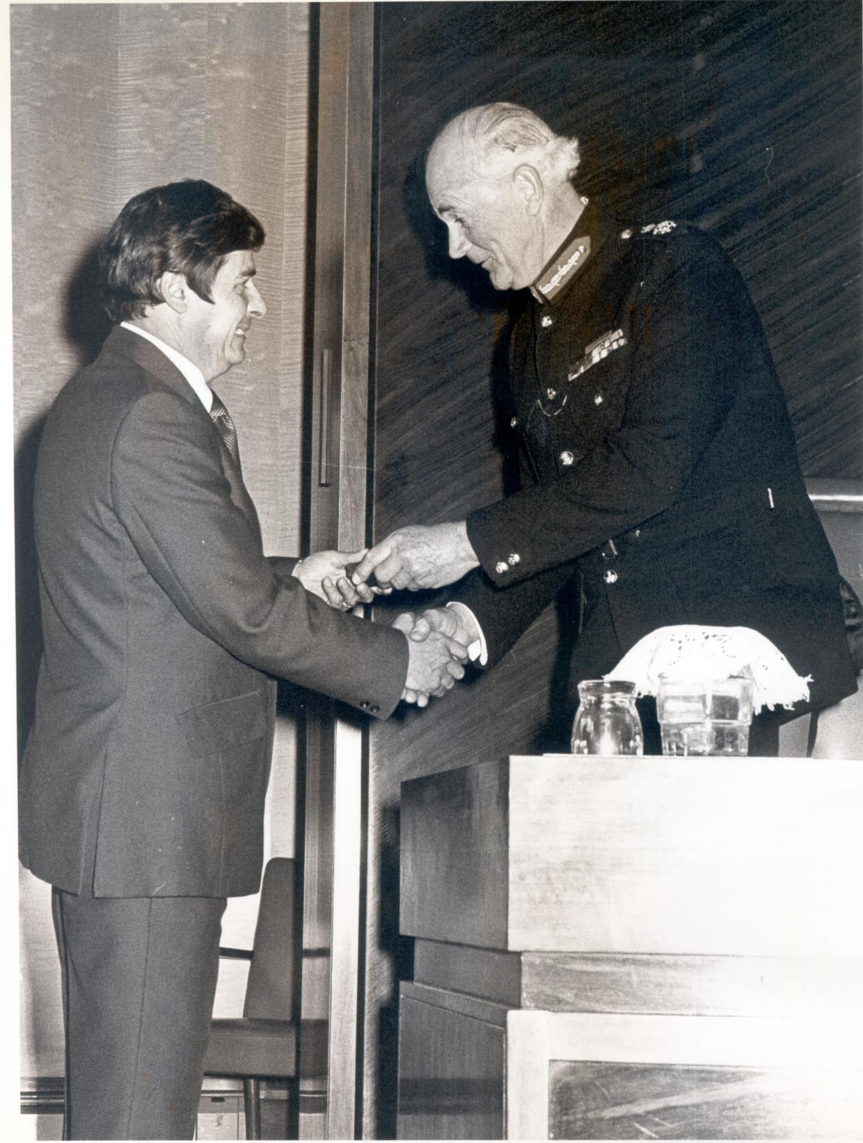 Presentation of Queen's Commendation for Brave Conduct to Detective Constable Brian Watkins by Lord Lieutenant of Gloucestershire Colonel Gibbs 10.3.1982 . (Gloucestershire Police Archives URN 399)