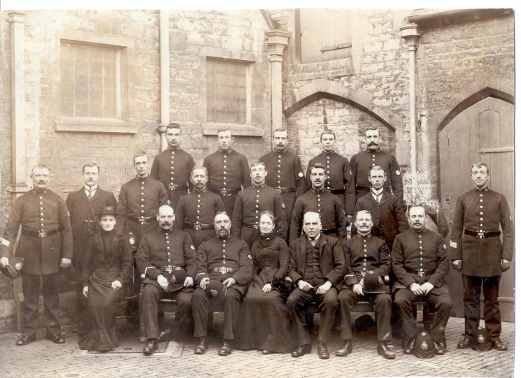 Group of officers at the retirement of Superintendent Morgan, Cirencester, 1902. Back row left to right: Jones, 227 Lester, Wiggins, Corbett, Wiggins. Middle row: Sergeant 81 Hope, Long (the Superintendent's groom), Police Constables 256 Gasside, 299 Hiron, Read, 180 Wayman, Wade. Front row: Mrs Hope, Police Constables 181 Brotherton, Cleavely, Mrs Morgan, Mr Morgan, Police Constables Cove, Hands, Neville (Gloucestershire Police Archives URN 43)