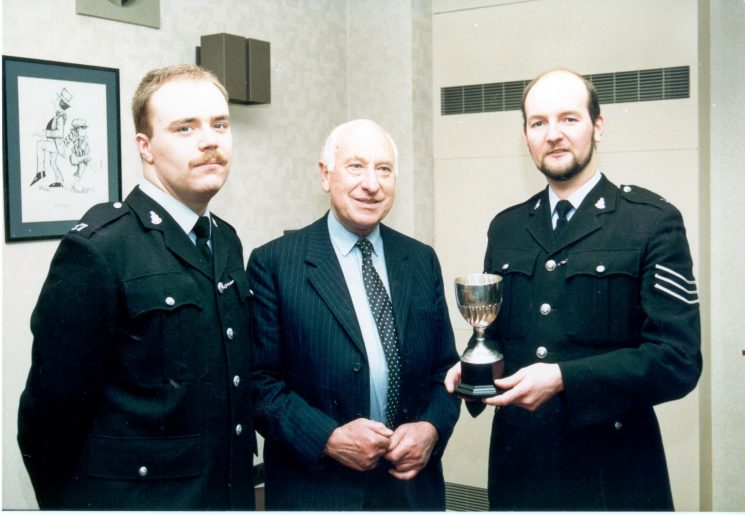 Presentation of Colburn Trophy by Mr Oscar Colburn  Commander British Empire; Justice of the Peace; Deputy Lieutenant  to Police Sergeant  David Peake and runner up Police Constable Stephen Radcliffe. (Gloucestershire Police Archives URN 474)