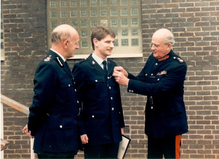 Presentation of Queen's award for Brave Conduct as a result of the 1987 Gloucester Police Station Siege. Police Constable Bill Matthews ( Bamfurlong) receiving his award from the County Lord Lieutenant Colonel Martin Gibbs with Chief Constable Albert Pacey. (Gloucestershire Police Archives URN 484)