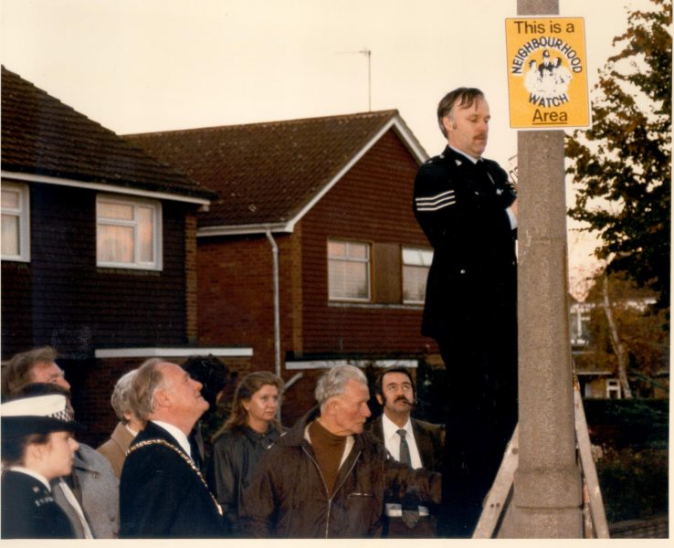 Police Sergeant Cliff Carter of  Community Services Department erecting the county's first Neighbourhood Watch Sign at Benhall, Cheltenham. (Gloucestershire Police Archives URN 490)