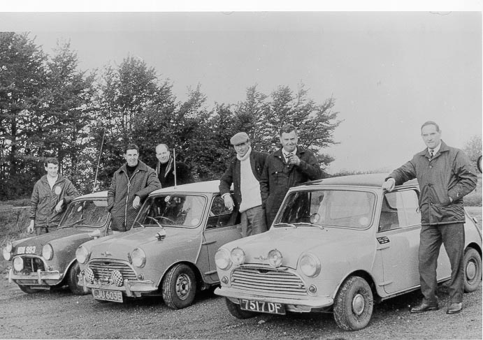 Police officers with Minis  (privately owned) prior to a Mini rally 1967. Officers include Police Sergeant Ken Hughes, Police Sergeant  L. Abbott, Police Constable Brian Marshall, Police Constable Roy Fitz, Police Constables Ron Savage and Andrew Hampton. The event was the Nightwatch Rally, organised by the Federation of British Police Motor Clubs, this event was in 1967 The crew of the last mini in line, WBW993, were Constable Anton Turner who was in charge at Berkeley Road on the A38. The driver was Constable Andrew Hampton. All three cars completed the rally, but no silverware. The car driven by Ron Savage had been borrowed from a local garage! (Gloucestershire Police Archives URN 598) | Thanks for further information to A.G. Hampton
