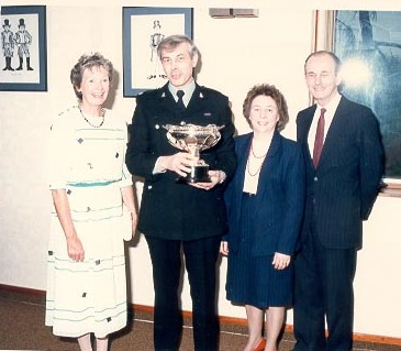 Police Constable Rod Gurney receiving the Caroline Symes Memorial Trophy (1980s) pictured with his wife and Mr and Mrs Symes. (Gloucestershire Police Archives URN 619)