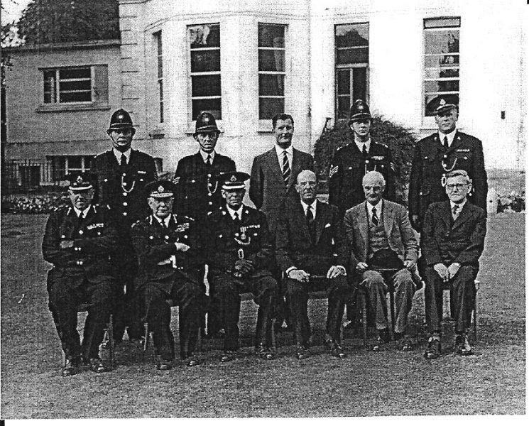 Award of long service medals and Queens Police Medal. Standing Left to right:  L. Wyatt, F. Young, D. Trapp, C. D. B. Williams, P. Foice Seated: Assistant Chief Constable A. H. Carter, Chief Constable  W. F. Henn, Superintendent C.F. Large Queens Police Medal, the Duke of Beaufort, Colonel Godman (Police Committee) and G. Blagg (Chairman of Cheltenham Magistrates) 1956. (Gloucestershire Police Archives URN 657)
