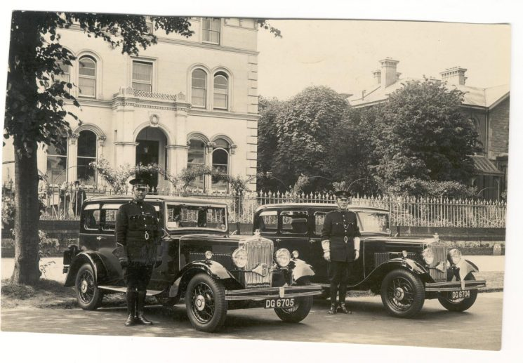 Two Morris motor cars and Police Constables H.J. Greenall and A. Finch outside Holland House 1933. (Gloucestershire Police Archives URN 81)