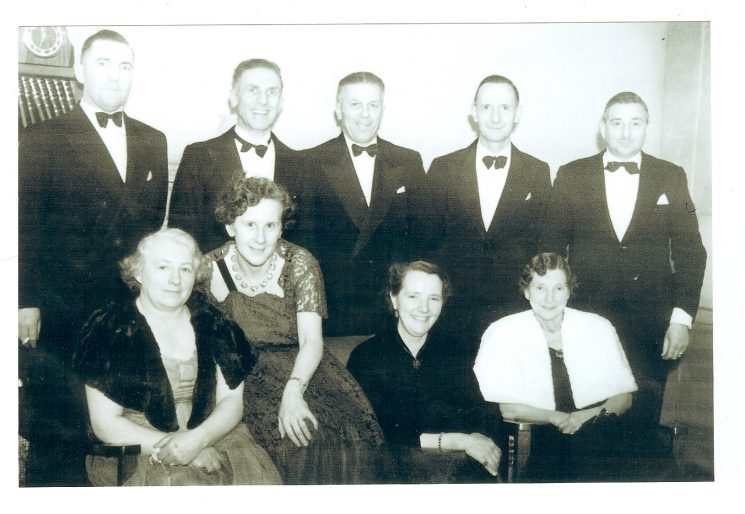 Officers and wives in evening dress 1950s. Back row right to left: H. J. Price, Horace Treadwell, Bill Hart, Jack Adshead, unknown. Front row right to left: Mrs Hart, Mrs Price, unknown,unknown. (Gloucestershire Police Archives URN 826)