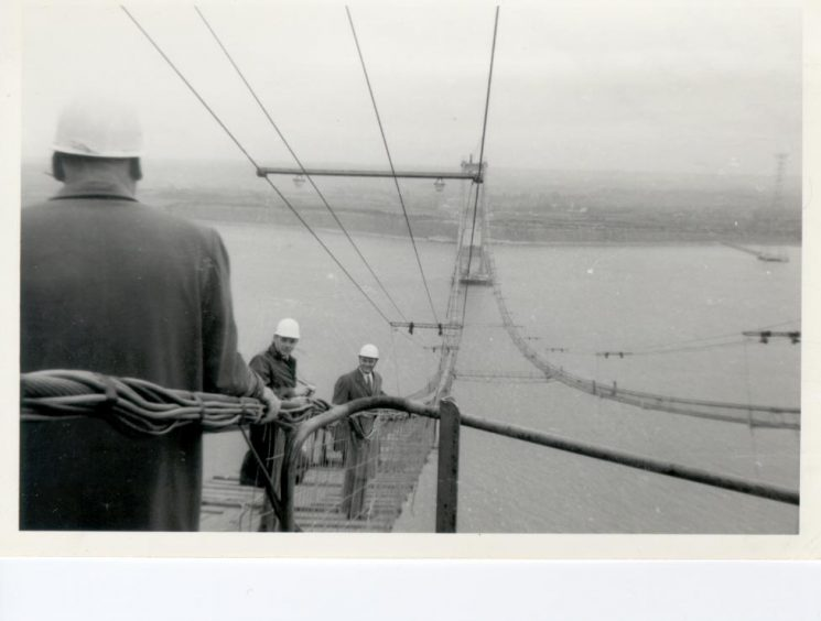 """Building of the Severn Bridge possibly 1964 when the main towers had been built, & the first lines had been """"spun"""" across from the two banks, enabling the walkway to be put in place. (Gloucestershire Police Archives URN 932)"""