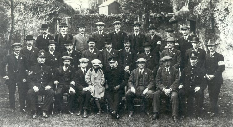 Winchcombe and District Special Constables - also shows unnamed Regular Superintendent , Police Sergeant  and Police Constable March 1919. This is suspected of being the earliest photo of Specials in Gloucestershire. It shows the Winchcombe Section in March 1919, sat front centre is Deputy Chief Constable Hopkins, sat far left is Police Sergeant O'Rourke, and sat far right is Police Constable Ford. During WWI the men were only issued with a lapel badge, duty armlet, a whistle and staff (Gloucestershire Police Archives URN 94)