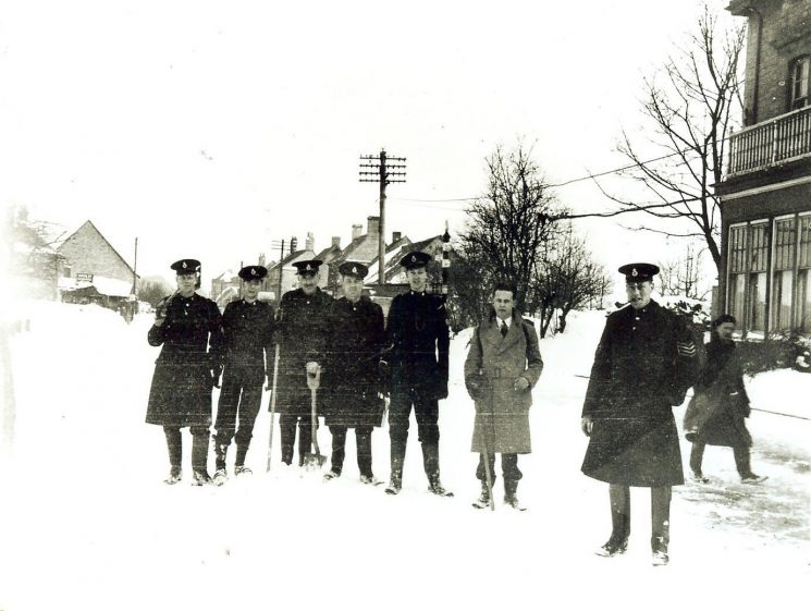 Staff at Birdlip having carried food supplies to cut-off village. Winter 1947 . Left to right Police Constable C.D.B Williams, Cadet R. Holloway,  Police Sergeant Norman Baker,Police Constable A. T. Nicholls, Inspector A. Miller, Police Constable C.Nicholls,  Cadet R.A.(Bob) Parker, Police Sergeant John Squires. (Gloucestershire Police Archives URN 944)