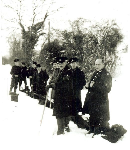 Staff at Birdlip having carried food supplies to cut-off village. Winter 1947. Police Sergeant Norman Baker, Police Sergeant John Squires. Cadet R.A. (Bob) Parker, Police Constable C.D.B. Williams, Cadet Trevor Jones, Cadet T. Holloway, Inspector Jock Millar, Inspector C. Walkeley, Police Constable Frederick A. Brookes, (Gloucestershire Police Archives URN 945)