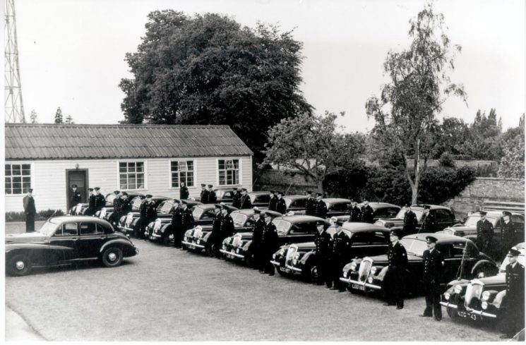 Seventeen patrol cars (Riley and Wolseley) lined up for inspection at rear of Police Headquarters  1954. (Gloucestershire Police Archives URN 948)