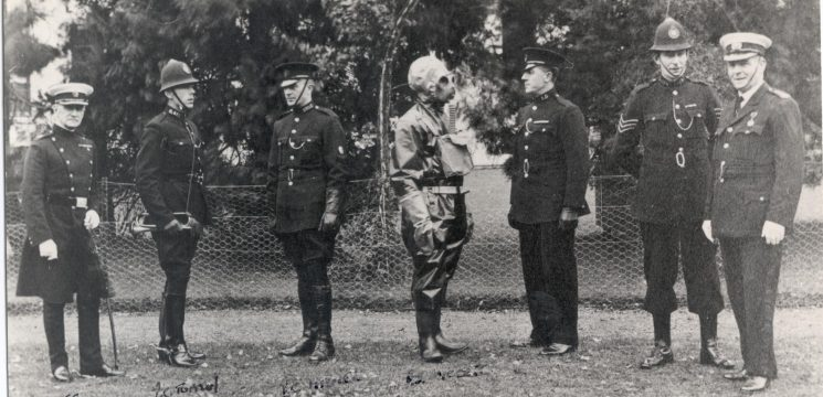 Staff Training - Gas protection equipment. Left to right: Chief Constable Stanley-Clarke, Mounted Patrol Officer Police Constable Tuffley, Motor Patrol Officer Richard Pole, In protective clothing- Police Sergeant Wiggett, Motor Patrol Police Constable (Unknown) Police Sergeant Matt Wilmott, Superintendent Joe W.P. Goulder. (Gloucestershire Police Archives URN 95)