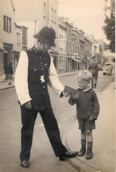 Police Constable Norman Stevens coming off 'Point Duty' at Stroud, showing unnamed boy (an evacuee from London) who regularly watched policemen doing this duty. Dated 1946. (Gloucestershire Police Archives URN 965)