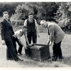 Police officers recovering a safe which had been stolen from the premises of Newman-Henders, Nailsworth, and found in a field near the factory. Date about 1946.  Shown in photo left to right. Press Reporter, Police Constable N. Stevens, Detective Sergeant Browning, and Police Sergeant Smith. (Gloucestershire Police Archives URN 967)