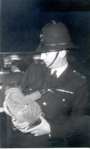 Old Barton Fair, Gloucester, showing Police Constable N Stevens with a street photographers monkey which had escaped and which he took into custody.  Monkey eventually returned to its owner. (Gloucestershire Police Archives URN 968)