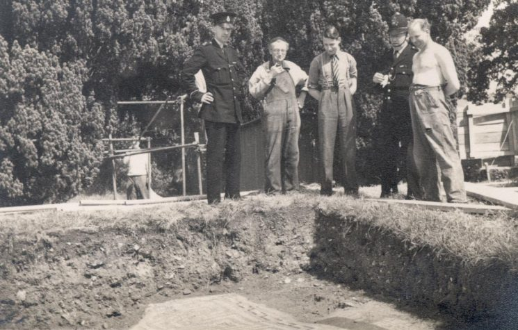 The uncovering of the Roman Pavement at Woodchester, Stroud. Thought to be 1951. Left to right Police Constable N. Stevens, unknown, Bill Brunt, Police Sergeant F. Smith,  unknown. (Gloucestershire Police Archives URN 969)
