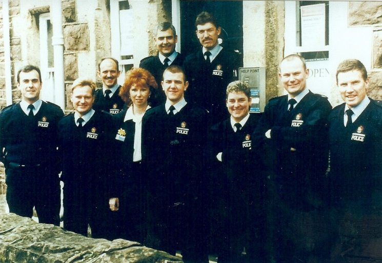 Staff outside Cinderford Police Station on the last day of Forest Division 31st March 1998. Back row left to right: Police Constable Paul Hutchinson,Police Sergeant Colin Heselton, Police Sergeant  Bob Phelps, Front row left to right: Police Constable Justin Parnell, Police Constable Dean Morse, Civilian Clerk Mary Parker (appointed Force Welfare Officer 2000) Police Constable John Cann, Police Constable Annette Gunter, Police Constable Andy Johnson, Police Constable Glen Morse.(Gloucestershire Police Archives URN 1002)
