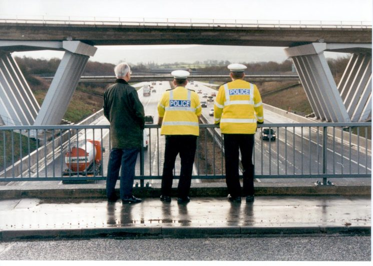 Former Chief Inspector Bob Parker with Police Constables Ian Kay and Stuart Kenny of Bamfurlong Traffic Station on the occasion of fiftieth anniversary of Bob Parker joining the Traffic Division at Lydney in 1948. Photographs taken on bridge of M5 motorway. (Gloucestershire Police Archives URN 1031-1)
