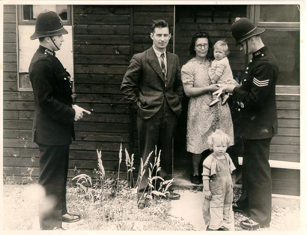 Police Sergeant Ernest W. Slade and Police Constable Arthur Meadows of Painswick Police Station talking to first squatters in Gloucestershire at Cranham, near Painswick. 1946. In August 1946 thousands of people mainly ex servicemen moved into empty properties around the country. Most of these properties were disused military camps. At one time there were an estimated 45,000 squatters in total some of them squatted until the mid 1950s. (Gloucestershire Police Archives URN 1113)